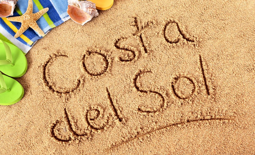 The words Costa del Sol written on a sandy beach with beach towel, starfish and flip flops.